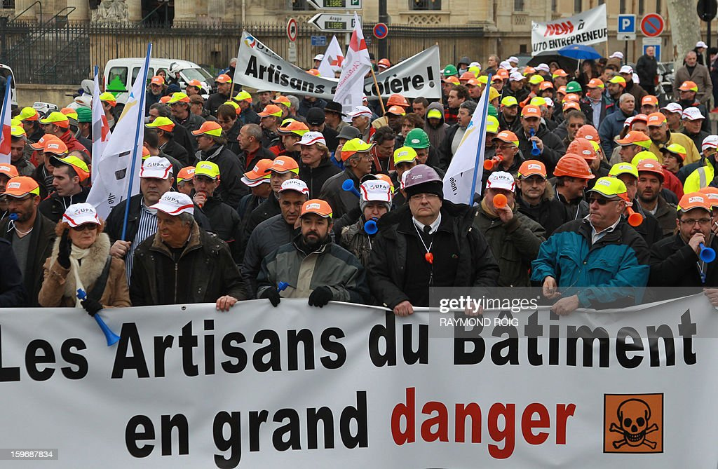Independent professionals in the building sector take part in a demonstration called by the Union Craft of the Region Pyrenees-Orientales (Union Professionelle Artisanale des Pyrenees-Orientales) in a street of the French southwestern city of Perpignan on January 18, 2013. Banner reads : 'Craftsmen of the building in great danger' AFP PHOTO / RAYMOND