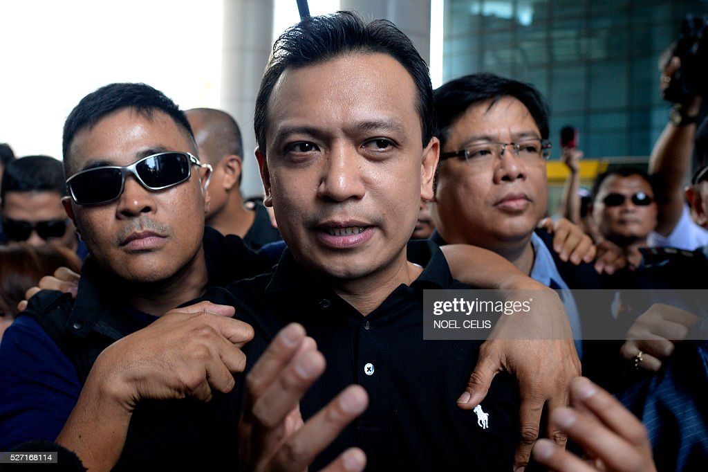 Independent vice presidential candidate Antonio Trillanes (C) is escorted by his aide as he leaves the premises of the Bank of the Philippine Island (BPI) in Manila on May 2, 2016. Trillanes has accused leading presidential candidate Rodrigo Duterte of hiding unexplained wealth deposited in secret accounts in the BPI and dared Duterte to open his bank records for public scrutiny. / AFP / NOEL