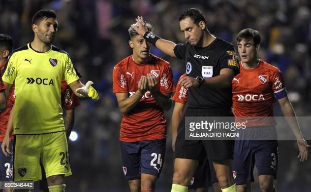 Independiente's forward Ezequiel Barco and goalkeeper Martin Campana argue with Argentinian referee Fernando Rapalini after he sanctioned them with a...