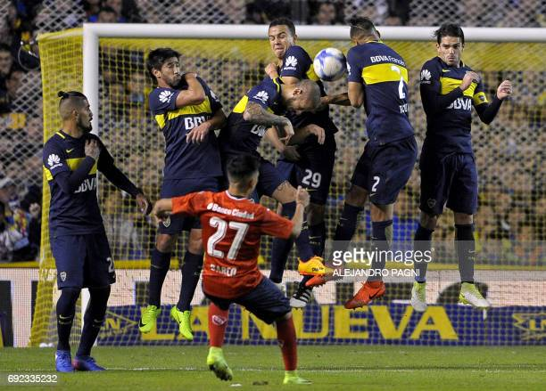 Independiente's forward Ezequiel Barco shoots a free kick over Boca Juniors' footballers during their Argentina first divsion football match at La...