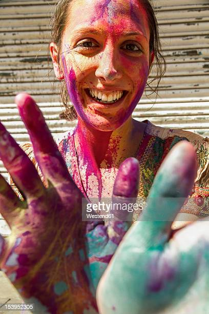 India, Ahmedabad, Young woman with colourfull hands and face on holi festival