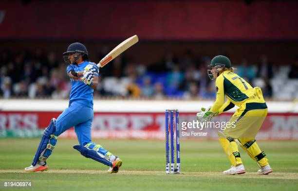 India batsman Harmanpreet Kaur hits out watched by Alyssa Healy during the ICC Women's World Cup 2017 SemiFinal match between Australia and India at...