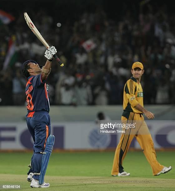 India batsman Sachin Tendulkar raises his bat after his century as Australia captain Ricky Ponting looks on during the 5th ODI between India and...
