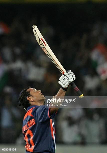India batsman Sachin Tendulkar raises his bat after his century during the 5th ODI between India and Australia at Rajiv Gandhi stadium Hyderabad