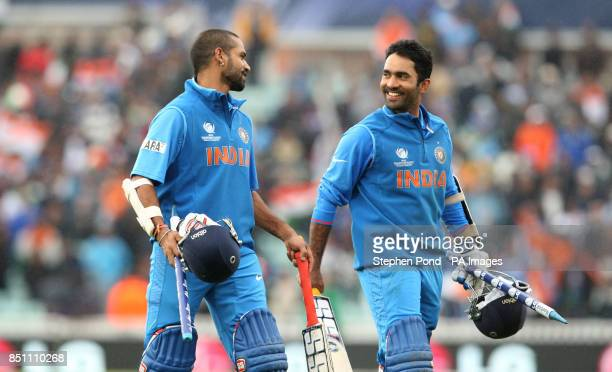 India batsmen Shikhar Dhawan and Dinesh Karthik leave the field after victory against West Indies during the ICC Champions Trophy match at the Kia...