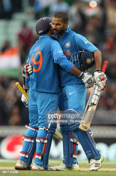 India batsmen Shikhar Dhawan celebrates his century with Dinesh Karthik during the ICC Champions Trophy match at the Kia Oval London