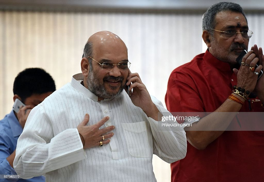 India Bharatiya Janata Party (BJP) President Amit Shah (L) talks on a mobile telephone as he arrives for a BJP Parliamentary committee meeting in New Delhi on May 3, 2016, / AFP / Prakash SINGH