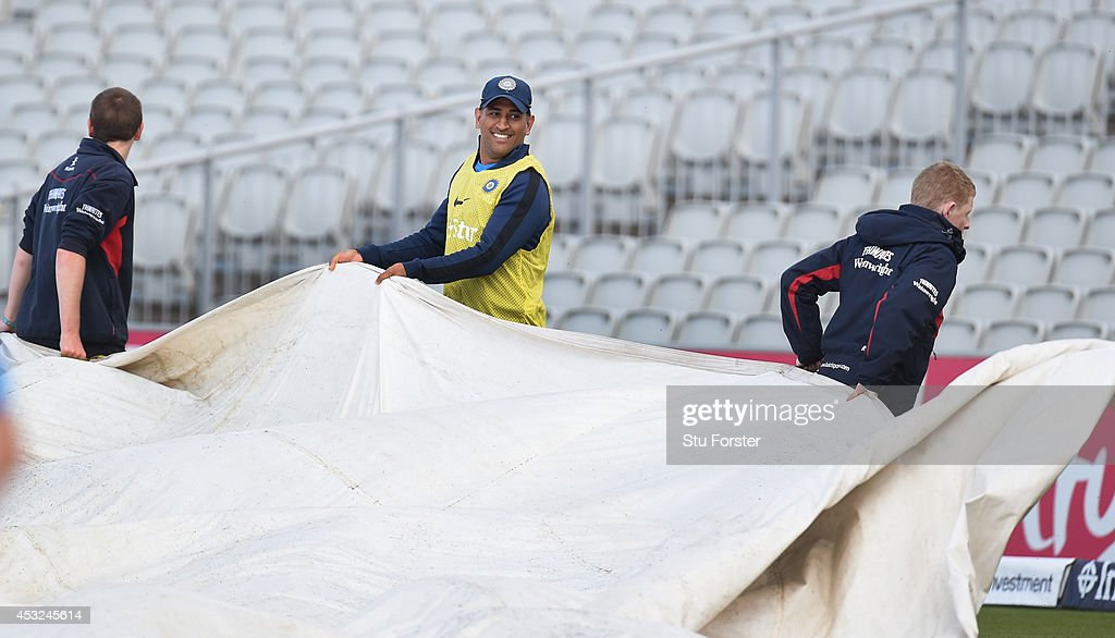 India captain Mahendra Dhoni (C) raises a smile as he helps the groundstaff remove the covers during India nets ahead of the 4th Test match between England and India, at Old Trafford on August 6, 2014 in Manchester, England.