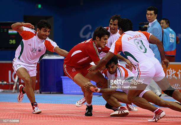 India capture Naser Roomiani Nazari of Iran as he tries to raid for points during the Men's Kabaddi final at Nansha Gymnasium during day fourteen of...