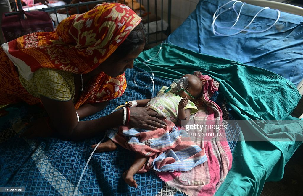 India child Bobiul Ahmed, who is three months old and who is suffering from Japanese encephalitis, is comforted by her mother while being treated at the North Bengal Medical College Hospital (NBMCH) on the outskirts of Siliguri on July 23, 2014. Outbreaks of encephalitis in India have killed more than 150 people, with health officials on alert fearing the death toll could rise further, state government directors said. Some 102 people have died in West Bengal state from the mosquito-borne virus which affects mainly malnourished children and can cause brain damage and seizures, said medical education director Sushanta Banerjee. Many of the deaths have occurred since the onset of the monsoon season in June when mosquitoes breed in large numbers. AFP PHOTO/ Diptendu DUTTA