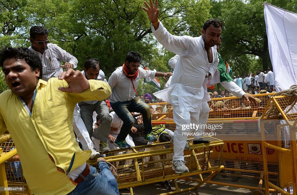 India Congress party workers jump over police barricades during the 'March for Democracy' protest against the National Democratic Alliance (NDA) government led by the Bharatiya Janata Part's (BJP) Narendra Modi in New Delhi on May 6, 2016. Former Indian prime minister Manmohan Singh, Congress Party President Sonia Gandhi and party Vice-president Rahul Gandhi were briefly arrested at a police station and later released during a 'Save Democracy' protest march against the ruling Bharatiya Janata Party (BJP). / AFP / PRAKASH