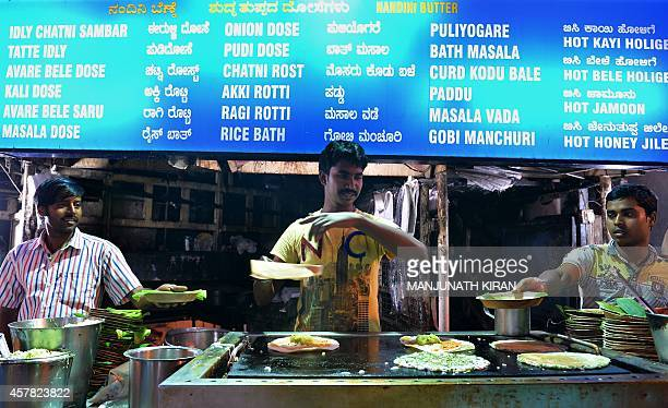 India cooks prepare the popular South Indian 'dosa' at a roadside stall in Food Street in Bangalore on October 24 2014 'Dosa' is a fermented crepe or...