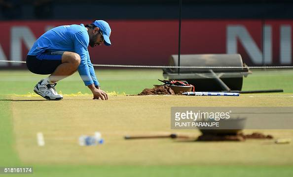 India cricket team captain Mahendra Singh Dhoni inspects the pitch at The Wankhede Cricket Stadium in Mumbai on March 30 2016 India plays their World...