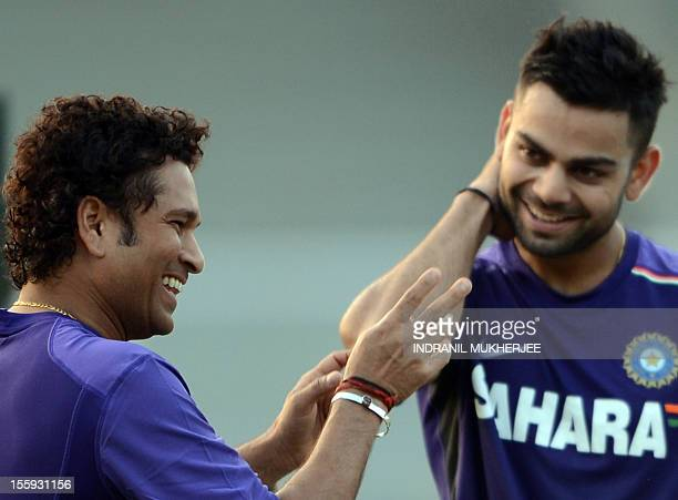 India cricketer Sachin Tendulkar shares a light moment with teammate Virat Kohli during a training session on the first day of a three day camp at...