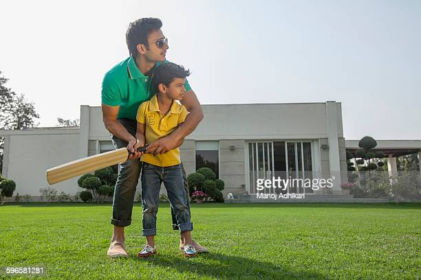 India, Father teaching young boy (4-5) to play cricket on backyard