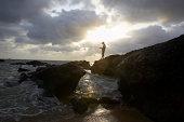 India, Goa, Kola Beach, man fishing on rocks, sunset