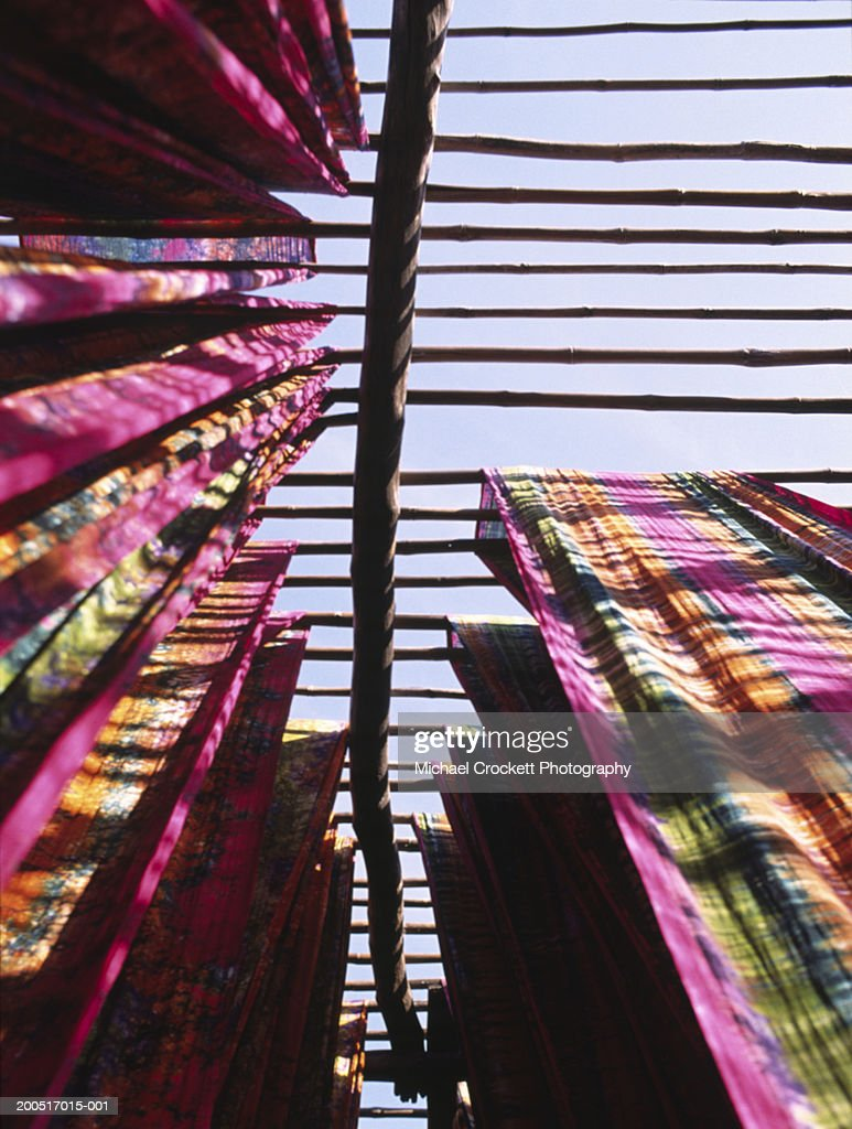 India, Gujarat, dyed fabrics drying on rack, low angle view : Stock Photo
