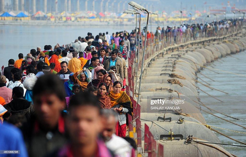 India Hindu devotees cross a pontoon bridge as they prepare to bathe at Sangam confluence of rivers Ganges Yamuna and mythical Saraswati to mark the...