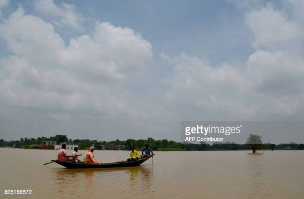 India Hindu monks from the 'Bharat Sevashram Sangha' socioreligious organisation use a boat to bring food donations to villagers affected by flooding...