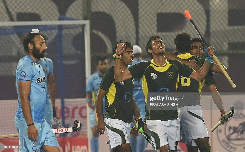 India hockey captain Sardar Singh walks past as Pakistan players celebrate a goal against India during their Hero Hockey Champions Trophy 2014 semi...