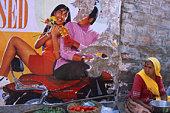 India, Jodhpur, Woman sitting by Bollywood poster
