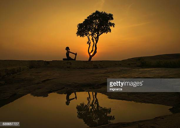 India, Karnataka, Hampi, Side view of woman doing Yoga asanas at sunset