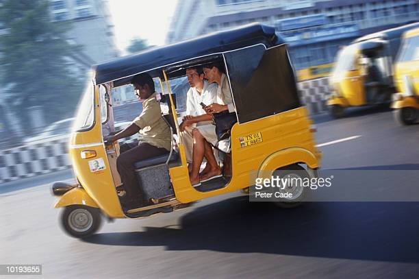 India, Madras, couple travelling in auto rickshaw (blurred motion)
