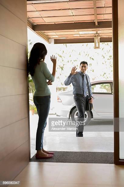 India, Man and woman waving goodbye at front door