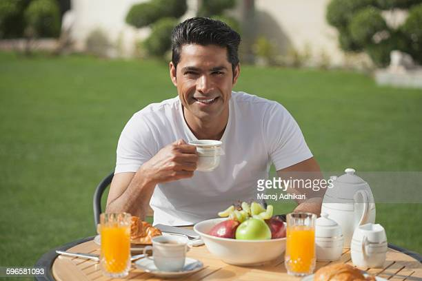 India, Man in white t-shirt having breakfast in garden