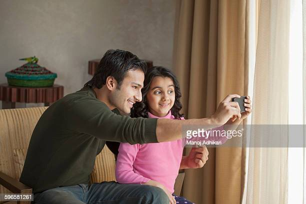 India, Man with daughter (6-7) sitting in armchair and taking selfie with mobile phone
