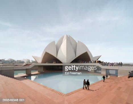 India, New Delhi, visitors walking by ornamental pond at Bahai Temple