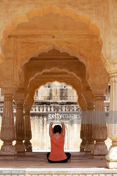 India, Rajasthan, Amber Fort, woman performing yoga, rear view