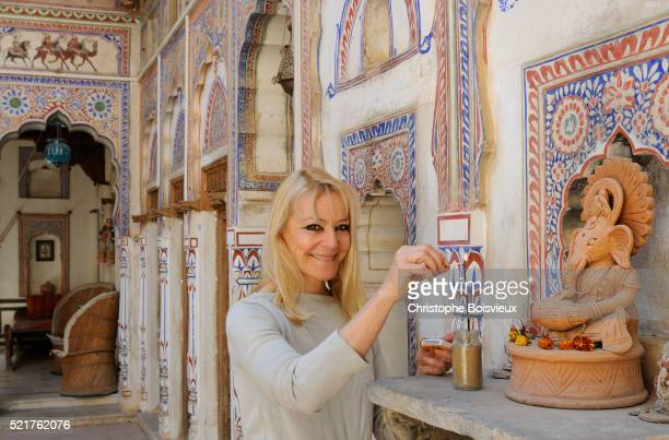 India, Rajasthan, Shekhawati, Fatehpur, Nand Lal Devra Haveli (1802), Haveli owner Nadine Le Prince lighting an incense stick before a clay statue of god Ganesh