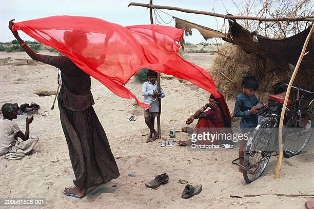 India, Rajasthan, woman holding scarf in wind standing outside hut