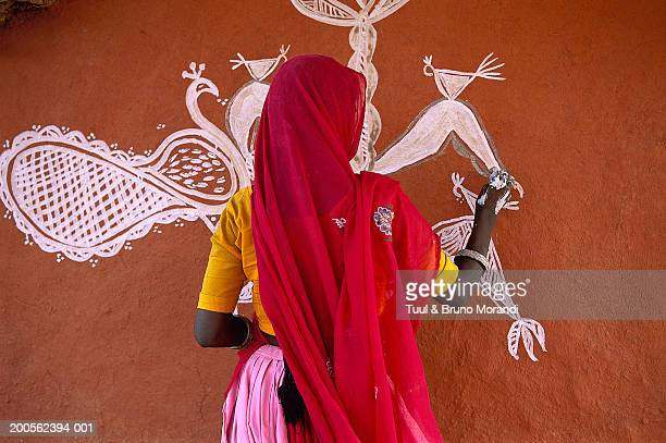 India, Rajasthan, Woman painting picture on wall, rear view