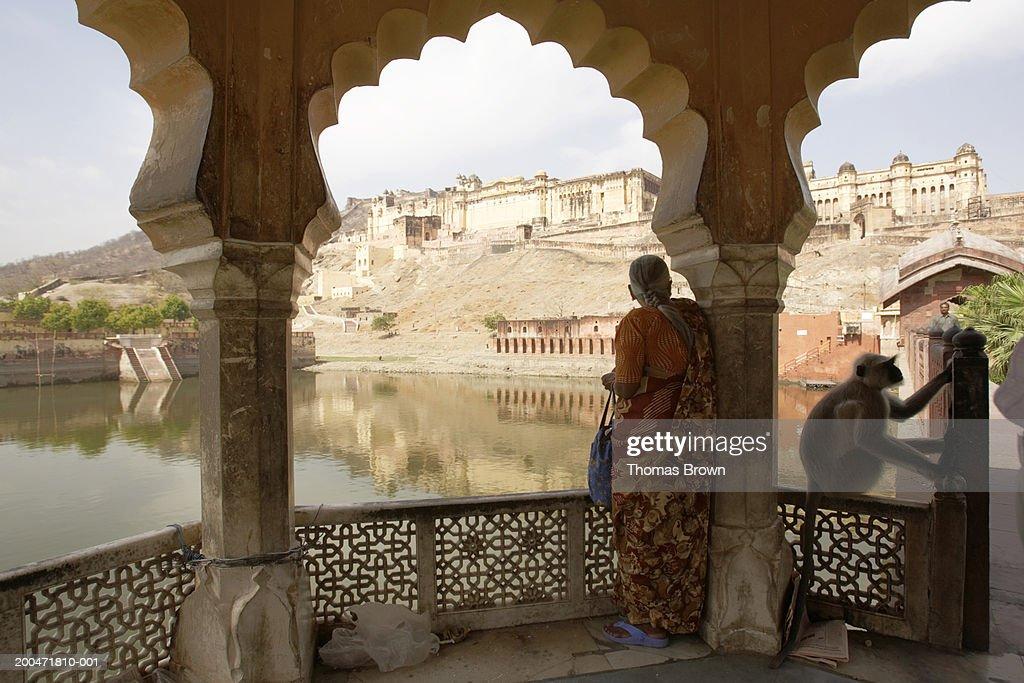 India, Rajasthan, woman standing on veranda, Amber Fort in distance : Foto de stock