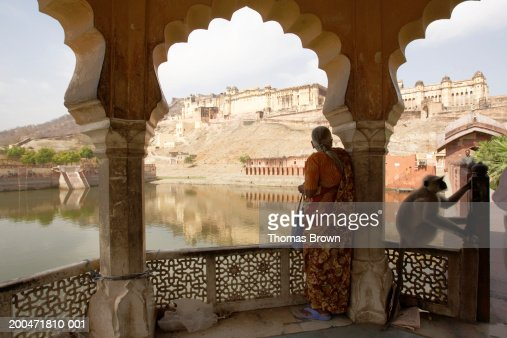 India, Rajasthan, woman standing on veranda, Amber Fort in distance : Stock Photo