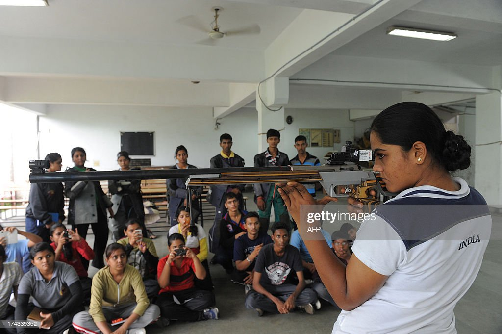 India shooter Lajja Goswami gives shooting tips to National Cadet Corps (NCC) members at the Ahmedabad Military and Rifle Training Association in Ahmedabad on July 24, 2013. Lajja recently clinched the silver medal in the women's 50-metre Rifle 3 Position event, at the International Shooting Sport Federation, ISSF World Cup in Granada, Spain. AFP PHOTO / Sam PANTHAKY
