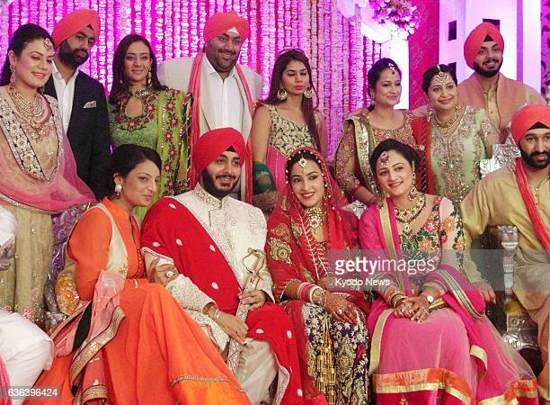 NEW DELHI India Sikh men and women in flashy attire pose for a photo at a wedding party in New Delhi on April 24 2013