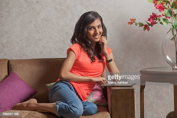India, Smiley young woman sitting on sofa