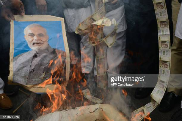 India supporters of the opposition Congress party burn old 500 INR notes and a poster bearing the imgage of Prime Minister Narendra Modi during a...