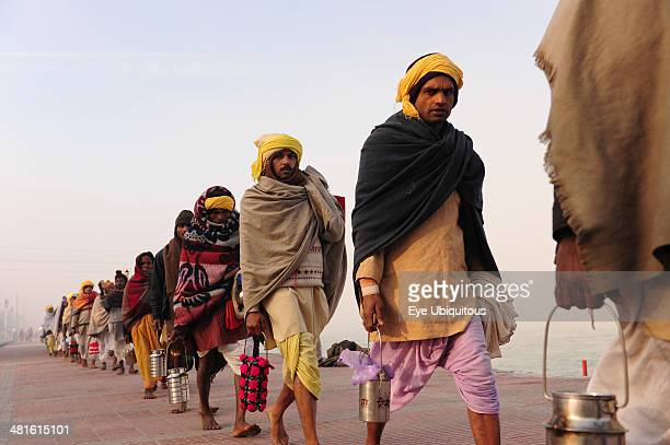 India Uttarakhand Haridwar Line of pilgrims carrying tiffin boxes during Kumbh Mela Indias biggest religious festival where many different traditions...