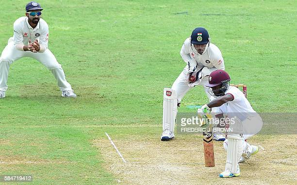 India wicket keeper Wriddhiman Saha catches the ball as Jermaine Blackwood of the West Indies is beaten off a delivery from bowler Ravichandran...