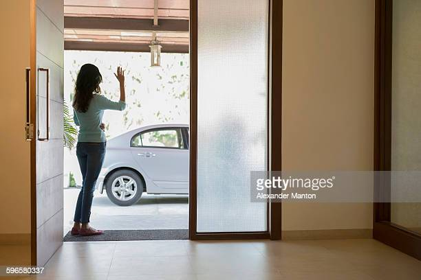 India, Woman waving goodbye at front door