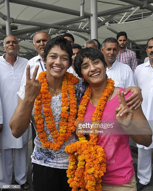 India women wrestlers Babita Kumari and Vinesh Phogat after arriving from the Commonwealth games in Glasgow at IGI Airport on August 2 2014 in New...