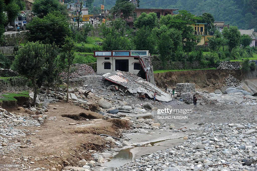 India workers are seen at a damaged house alongside the Mandakini river at Jawahar Nagar, in the flood affected area of northern Uttarakhand state on July 1, 2013. Construction along river banks will be banned in a devastated north Indian state amid concerns unchecked development fuelled last month's flash floods and landslides that killed thousands, the state's top official said July 1.