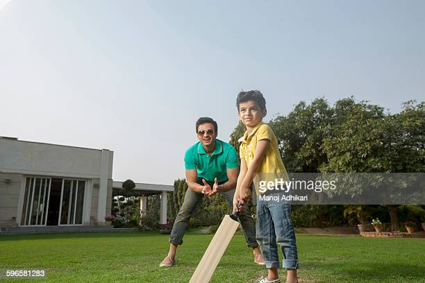India, Young boy (4-5) playing cricket with father on backyard
