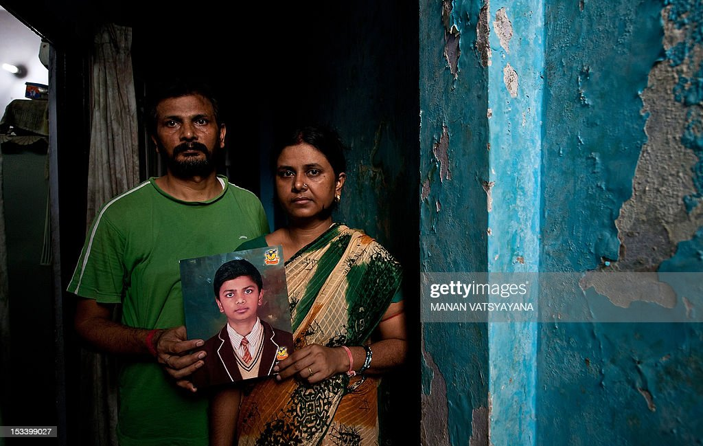 STORY 'India-children-crime,FEATURE' by Rupam Jain Nair In this picture taken on September 12, 2012, Pinki and Dinesh Kumar Singh pose with a photograph of their missing child Shivam Singh at their residence in New Delhi. Thirteen-year-old Shivam Singh promised his mother he would be back to do his homework as he ran to get some sweets. He never returned, becoming one of the 50,000 children who go missing every year in India. According to recent crime data, 14 children go missing in New Delhi every day, at least six of whom are victims of human trafficking. The United Nations Children's Fund (UNICEF) says around 1.2 million children are victims of child trafficking across the world every year. AFP PHOTO/ MANAN VATSYAYANA