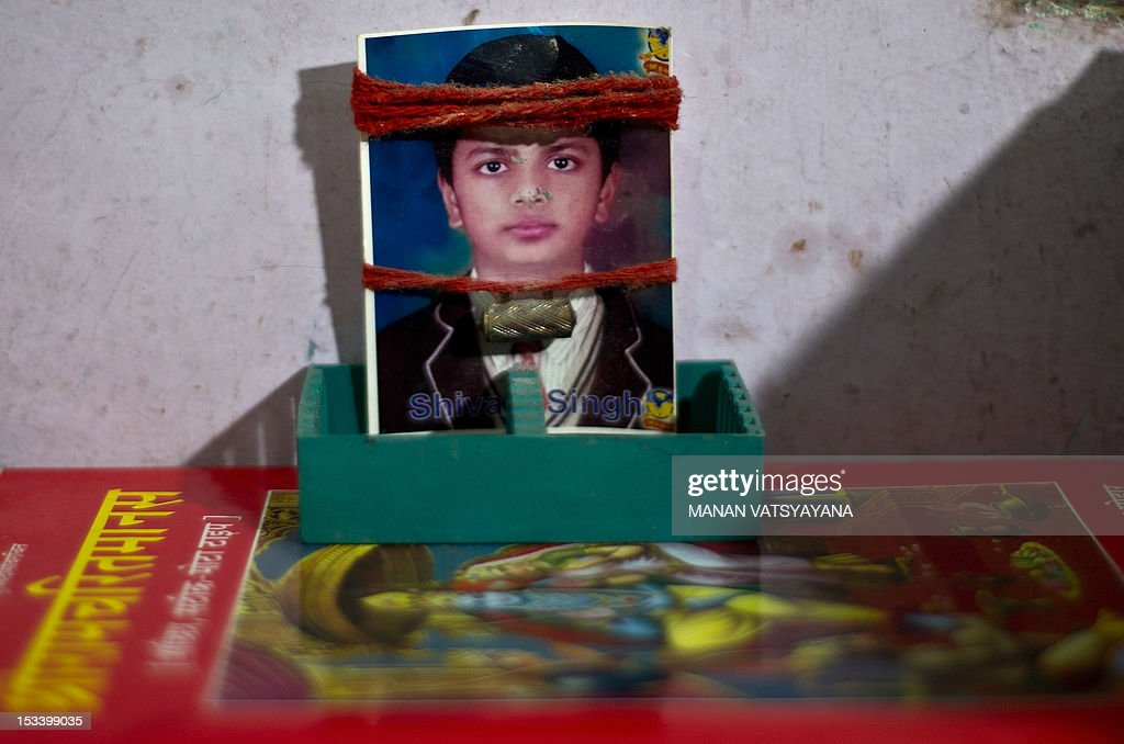 STORY 'India-children-crime,FEATURE' by Rupam Jain Nair In this picture taken on September 12, 2012, religious threads adorn a photograph of missing Indian child, Shivam Singh, at his family's residence in New Delhi. Thirteen-year-old Shivam Singh promised his mother he would be back to do his homework as he ran to get some sweets. He never returned, becoming one of the 50,000 children who go missing every year in India. According to recent crime data, 14 children go missing in New Delhi every day, at least six of whom are victims of human trafficking. The United Nations Children's Fund (UNICEF) says around 1.2 million children are victims of child trafficking across the world every year.