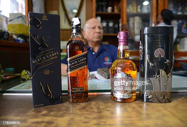 Indiaeconomyconsumersforexeducation by Penelope Macrae Indian businessman PRMan Singh poses beside bottles of imported alcohol at his store in...